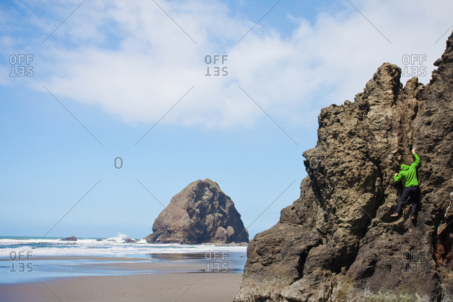 A man climbs a monolith in Pistol River State Park on the Oregon Coast, USA.