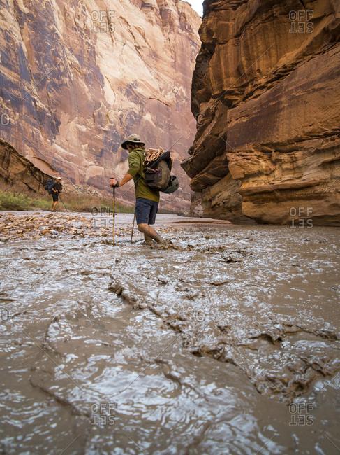A man hiking through a muddy creek in a canyon.
