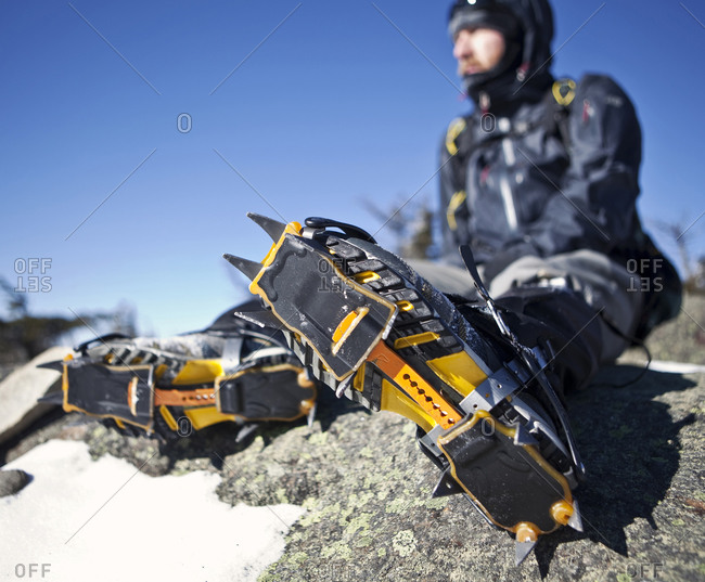 A mountaineer with crampons on rests on a rocky outcrop.