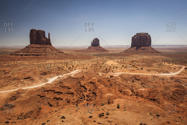 A road winds it's way among a desert landscape with buttes in the background.