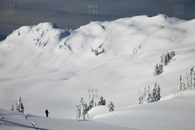 A silhouette of a backcountry skier with big mountains in the background.