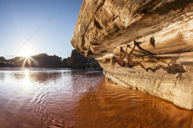 A woman bouldering above a red river.