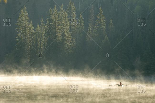 A woman rowing a scull boat a foggy morning near  Creede, Colorado.