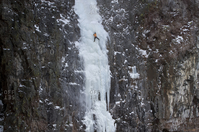 An ice climber ascending a frozen waterfall in Hyalite Canyon Montana.