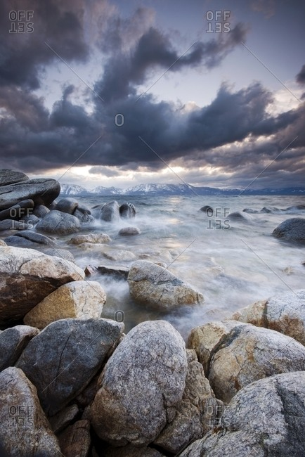 Dramatic clounds are illuminated over granite boulders and Lake Tahoe on the east shore of the lake as a storm approaches, Nevada.