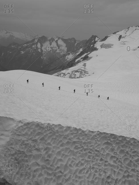 Explorers on a glacier trek on summertime snow.