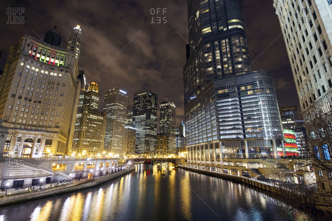 Looking down the Chicago River at the Chicago skyline and Trump Tower at night in Chicago, IL.