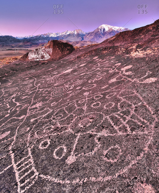 Piute Petroglyphs at sunrise with snow-capped Sierra in background, Eastern Sierra, California