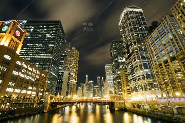Skyscrapers are illuminated along the Chicago River at night in Chicago, IL.