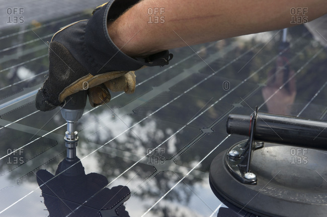 Solar installer fastening solar panel to roof with advanced technology.