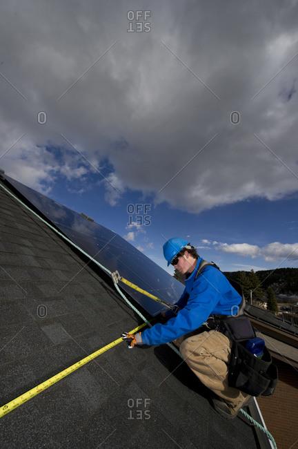 Solar installer works to expand a fremelesss solar installation.