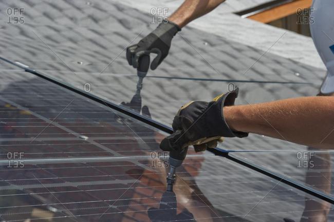 Solar installers work together on frameless installation.