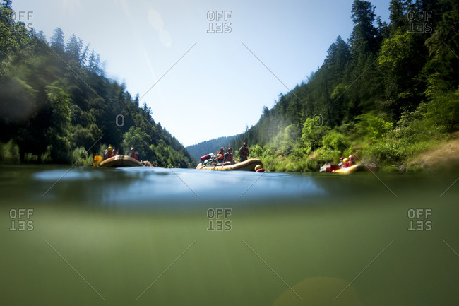 Split level view of rafters swimming from their rafts in the river.