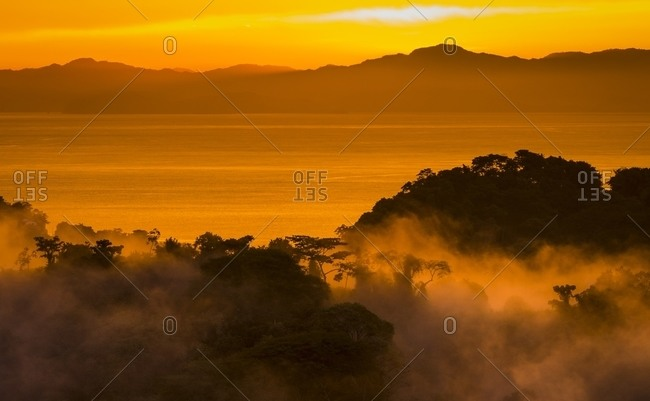 Sunset and glowing mist over tropical tree canopy and Gulf of Nicoya, Costa Rica
