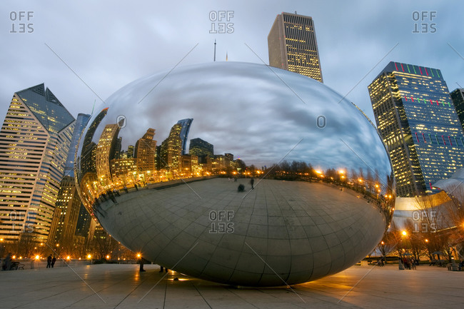 The Chicago skyline is reflected at dusk in the Cloud Gate sculpture informally known as The Bean in Millennium Park in Chicago, IL.