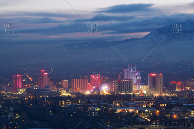 The Reno skyline is illuminated at dusk with clouds in the sky and snow covered peaks in the background in Reno, NV.
