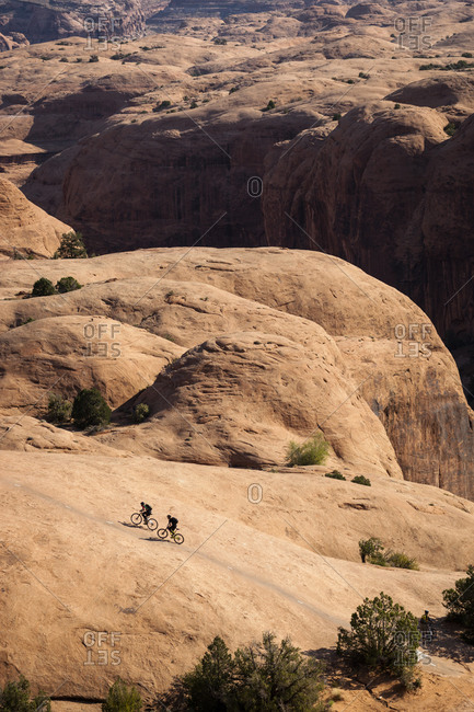 Two mountain bikers riding on slickrock.