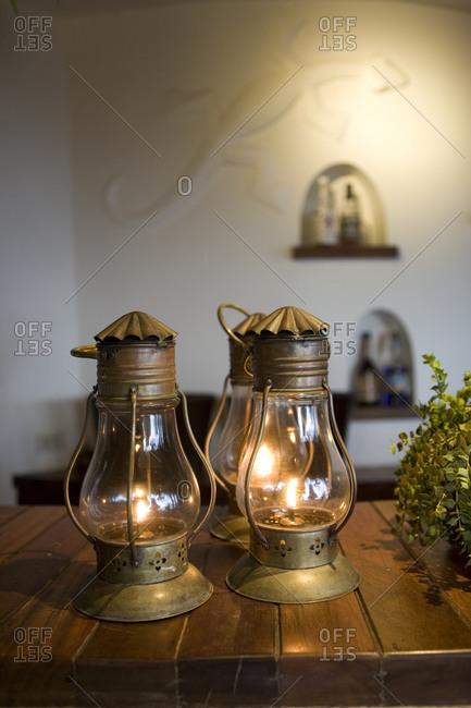Glimmering lanterns on wooden bar counter in Rayavadee Resort, Thailand