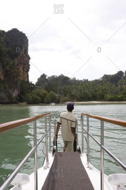 Sailor standing in prow of speedboat waiting for mooring