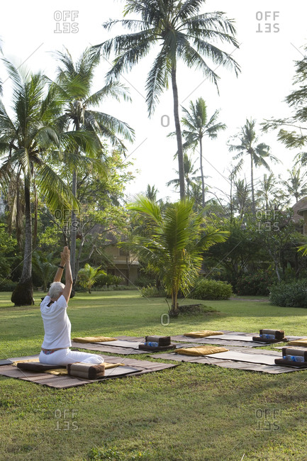 Senior woman doing yoga in tropical garden of five-star resort situated on southern Thailand�s Andaman coast