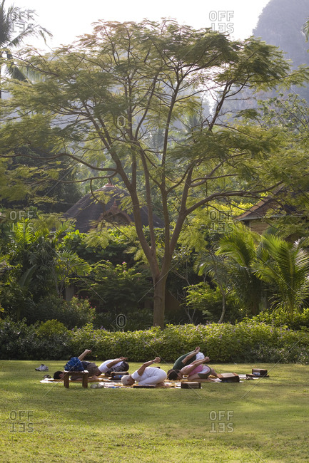 Group of people doing yoga in tropical garden of five-star resort situated on southern Thailand�s Andaman coast