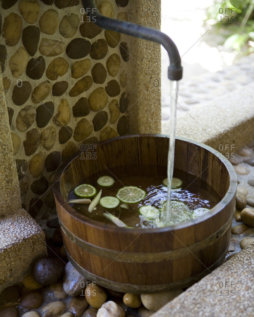 Filling wooden sauna bucket with water