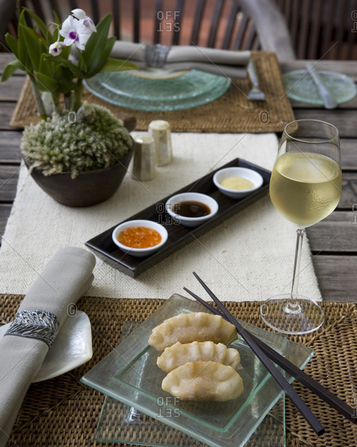 Traditional Asian stuffed dumplings with three different dips, glass of white wine on set table