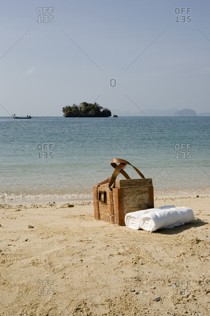 Picnic basket and rolled towels on sandy beach