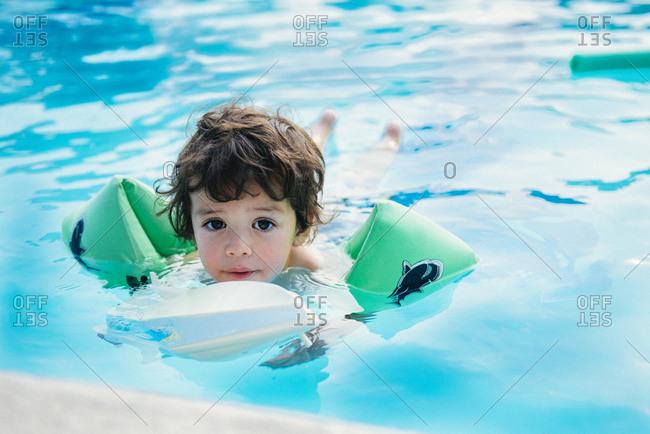 A boy floats in a pool
