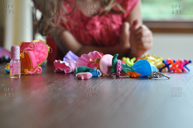 A little girl plays with plastic figurines