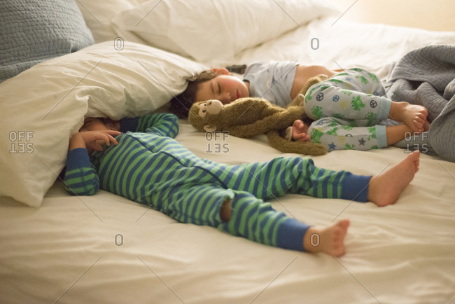 Two brothers asleep on a bed