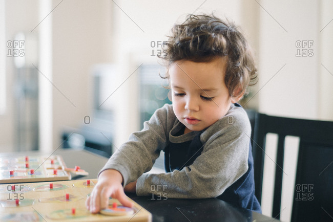 A little boy plays with a puzzle