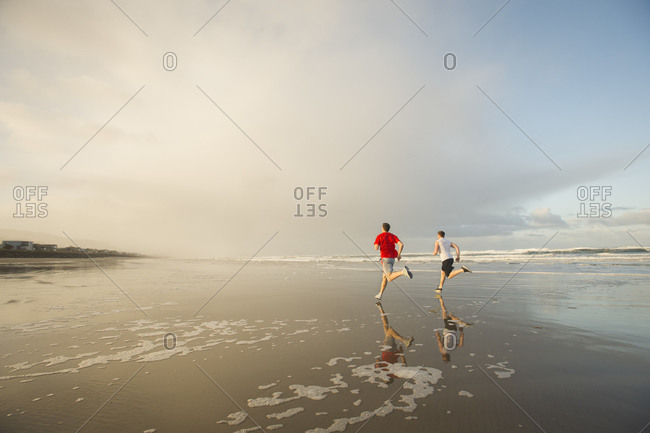 Young adult men running on beach