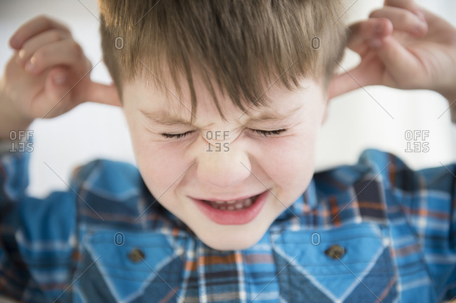 Portrait of boy (4-5) sticking fingers in his ears