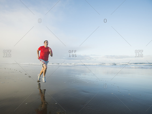 Young adult man running on beach