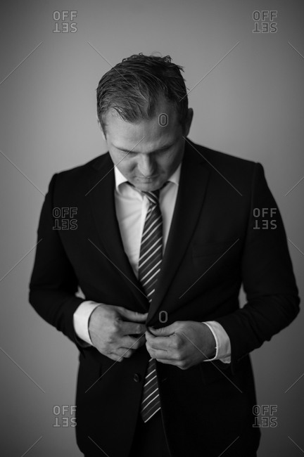 Businessman buttoning suit