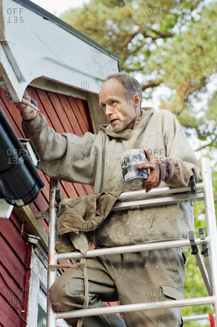 Man on ladder painting house stock photo - OFFSET