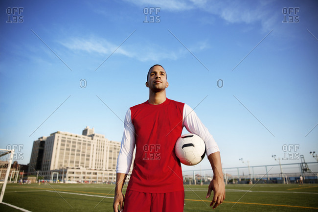 Young man standing on soccer field and holding a ball