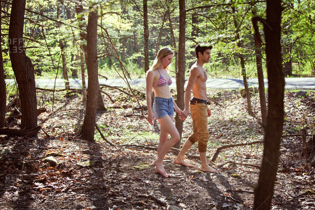 Couple walking in forest holding hands