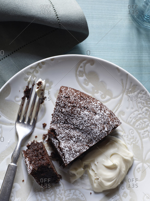 Slice of brownie cake with whipped cream on plate