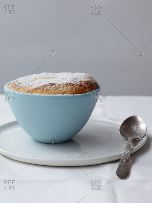 Lemon souffle served in cup with spoon on table