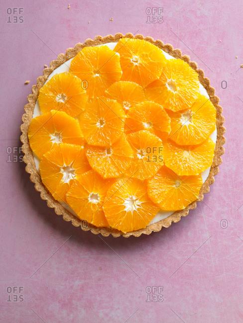 Orange tart on pink background