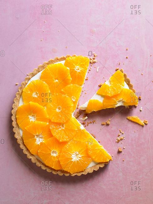 Sliced orange tart on pink background
