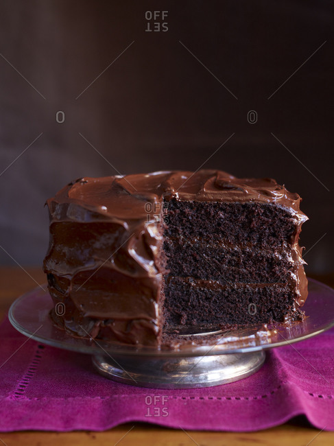 Devil's food cake with a slice missing on magenta napkin against dark background