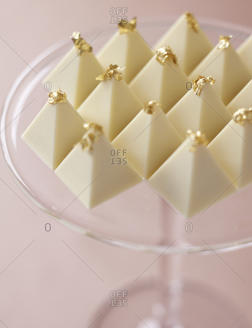 Close-up of white chocolate pyramids on a glass plate