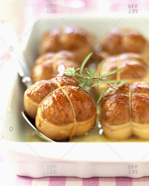 Tied roast veal parcels in casserole dish