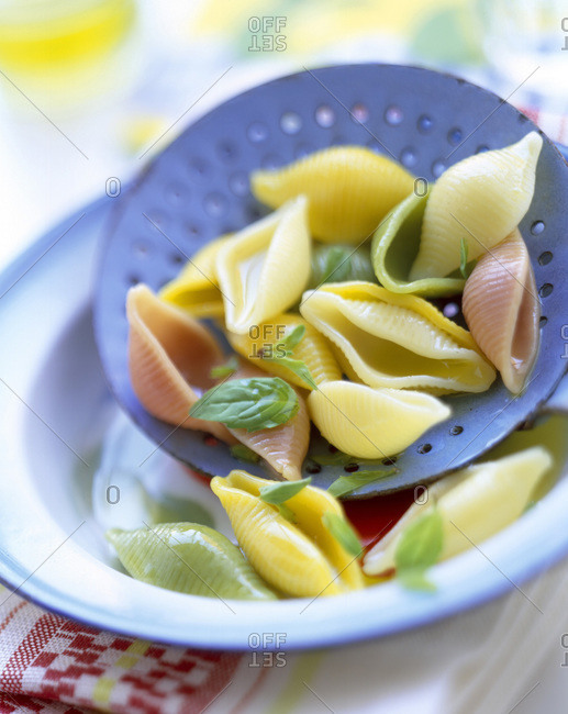 Conchiglie with basil in spoon colander