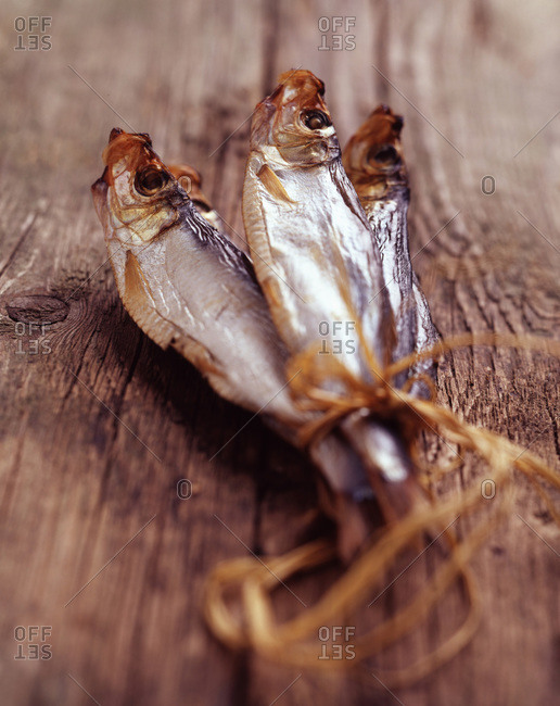 Tied dried Sprats on wooden table