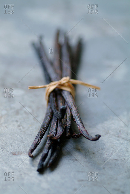 Bundle of vanilla pods on grey surface