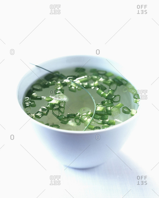 Broth in bowl with scallions